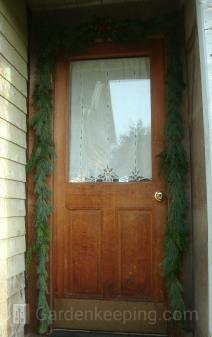 A pine and cedar garland. it's difficult to see, but there is a holly arrangement at the top.